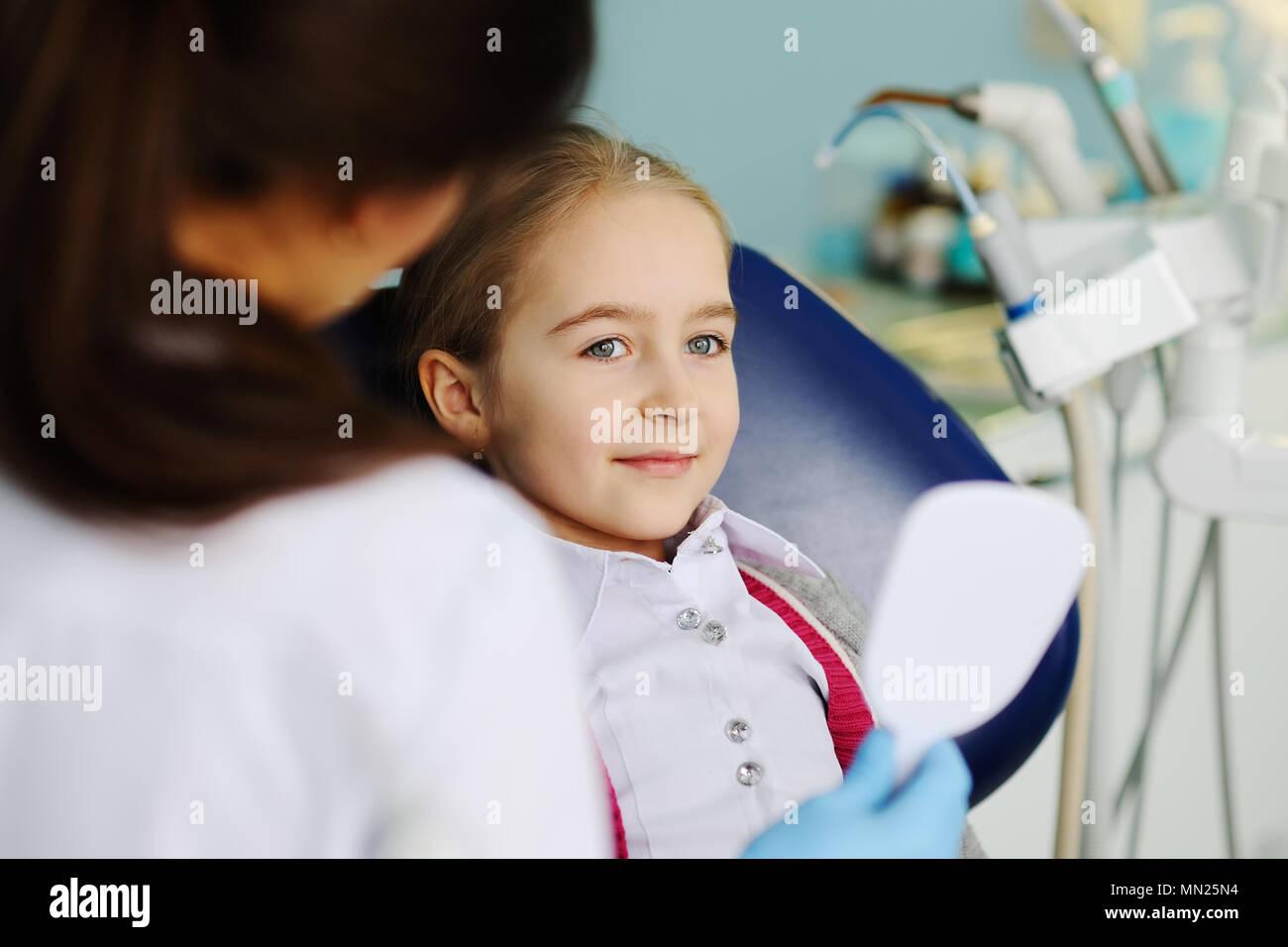 girl examines teeth in a dental mirror Stock Photo