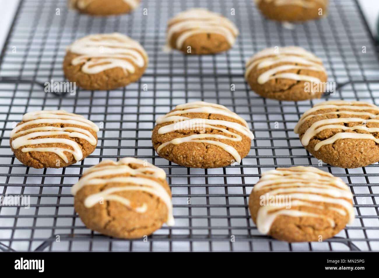 Freshly baked, homemade pumpkin spice cookies, with maple icing. These gluten and dairy free biscuits are displayed on a wire cooling. - Stock Image
