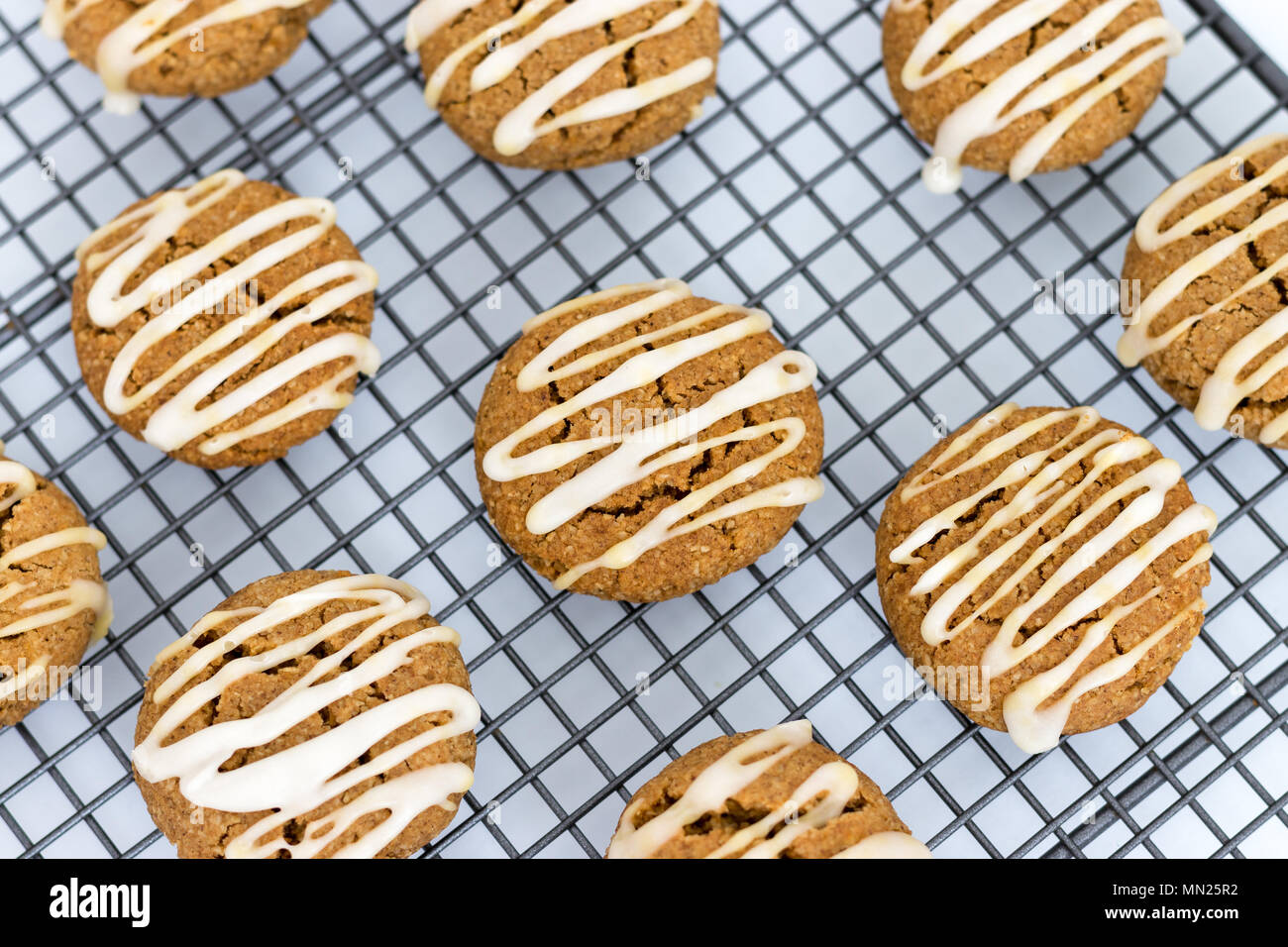 Freshly baked, homemade pumpkin spice cookies, with maple icing. These gluten and dairy free biscuits are displayed on a wire cooling. Stock Photo