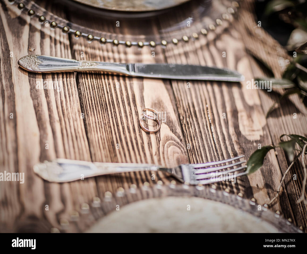 engagement rings and Cutlery on a wooden table - Stock Image