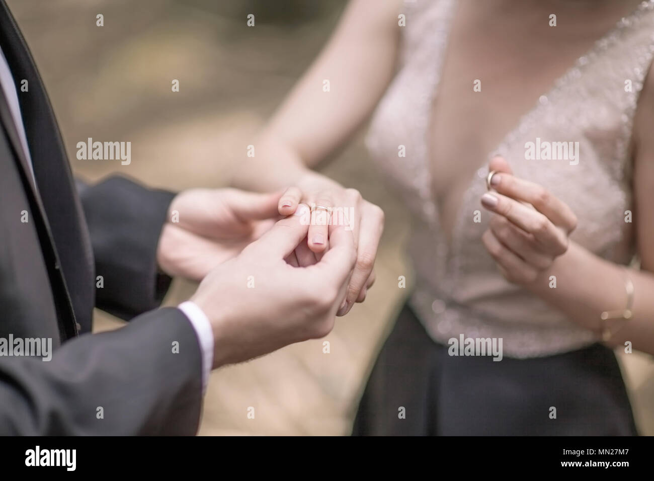 symbol of the beginning of family life: the couple exchange wedding rings - Stock Image