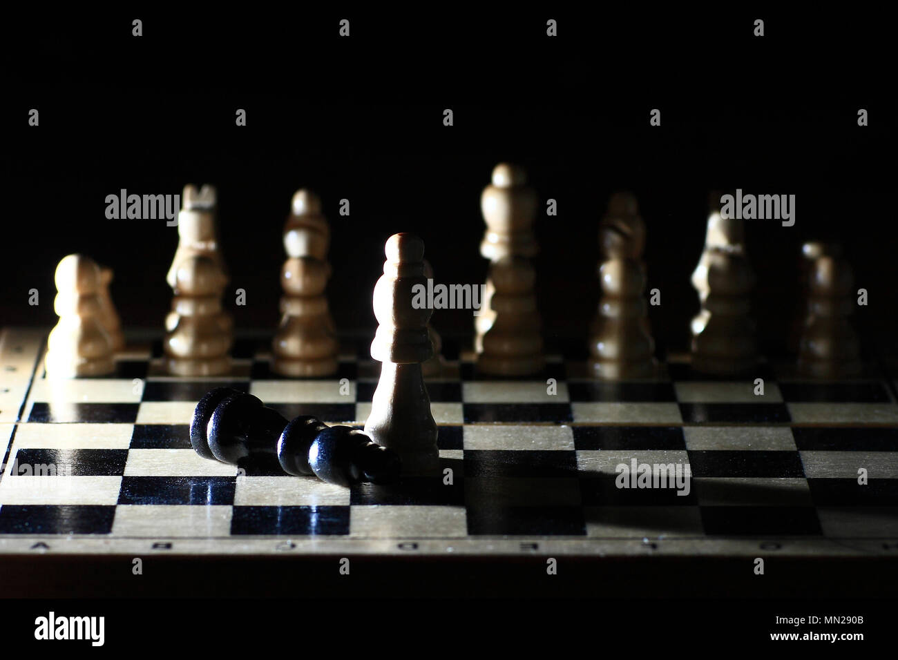 Composition with chessmen in the glossy chessboard - Stock Image