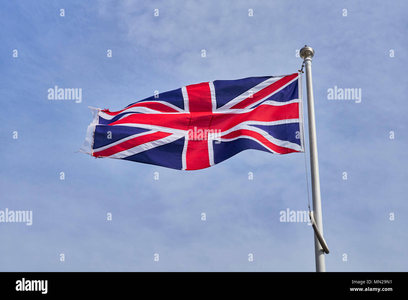 Union Jack flag fluttering in a light breeze on a flagpole against a pale blue sky - Stock Image