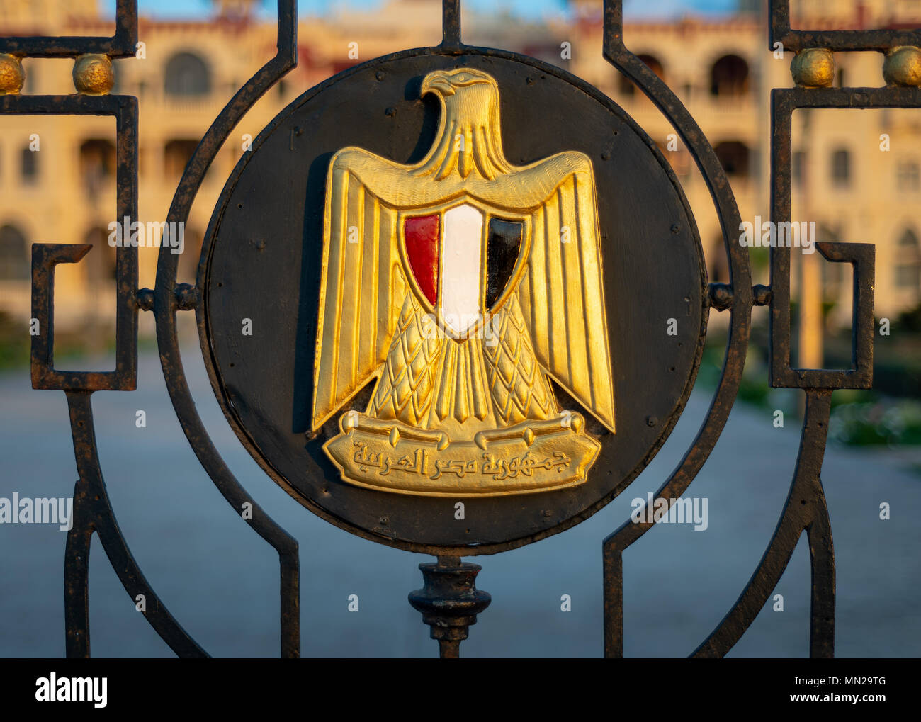 Logo of Egypt on an iron fence revealing Montaza Presidential Palace, consists of Golden Eagle of Saladin holding a scroll with Arabic text (Arab Repu - Stock Image