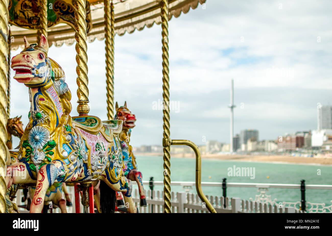 A view from Brighton Pier featuring the traditional horse carousel on the pier and the British Airways i360 observation tower in the distance. Stock Photo