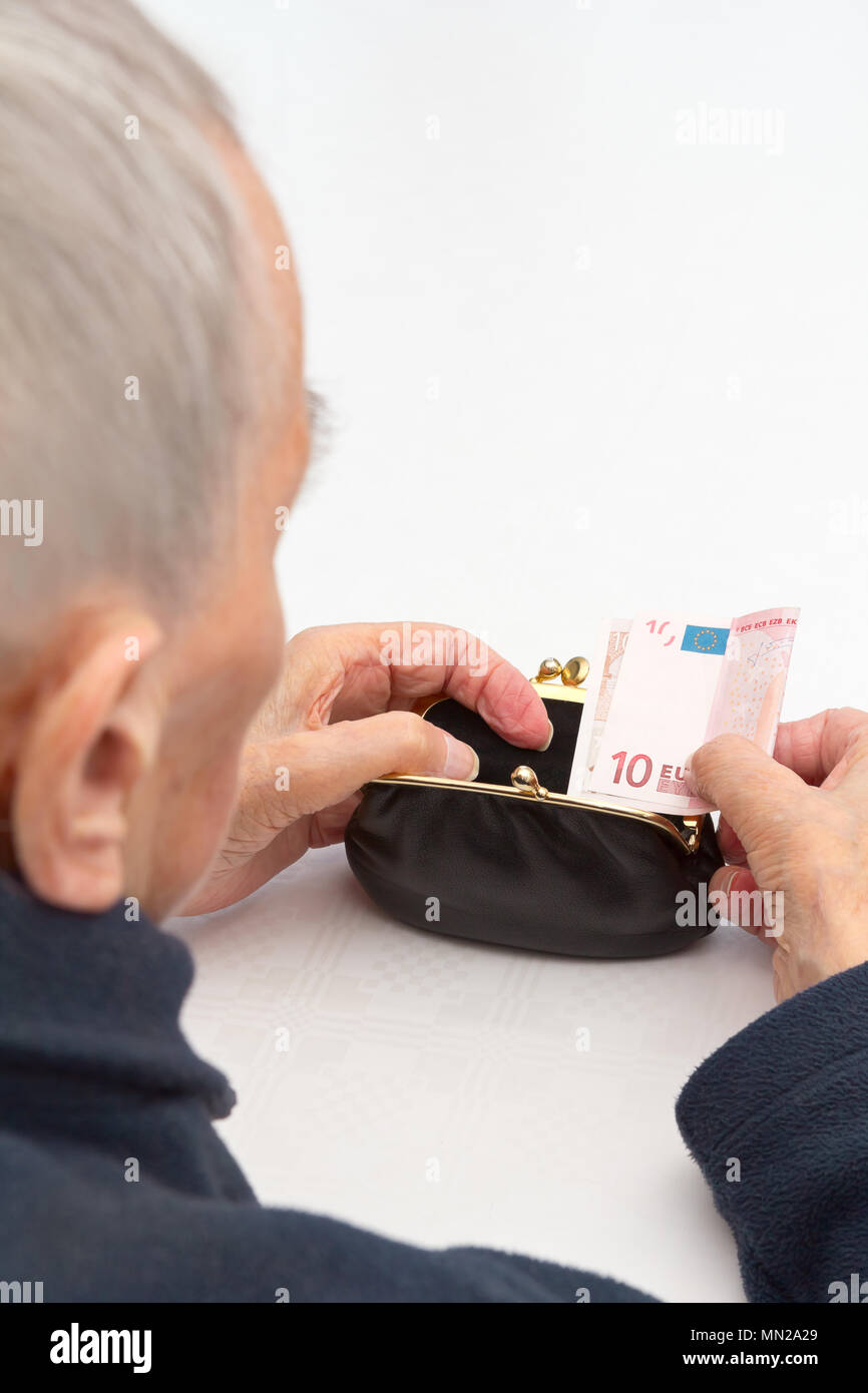 Senior woman holding an empty purse and a ten Euro banknote in her hands., copy or text space, old-age poverty concept - Stock Image