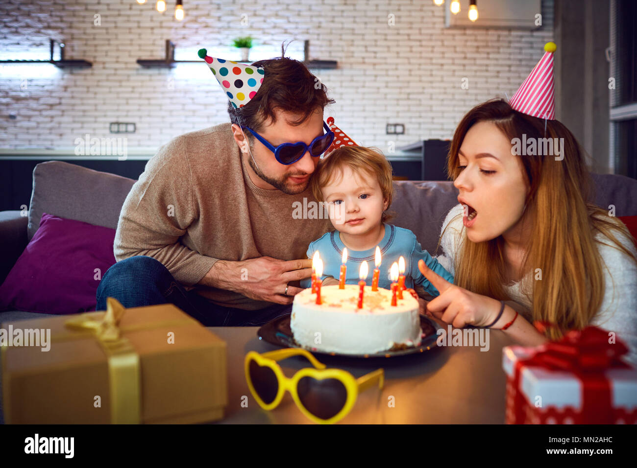 Parents with a cake  congratulate their child on his birthday. - Stock Image