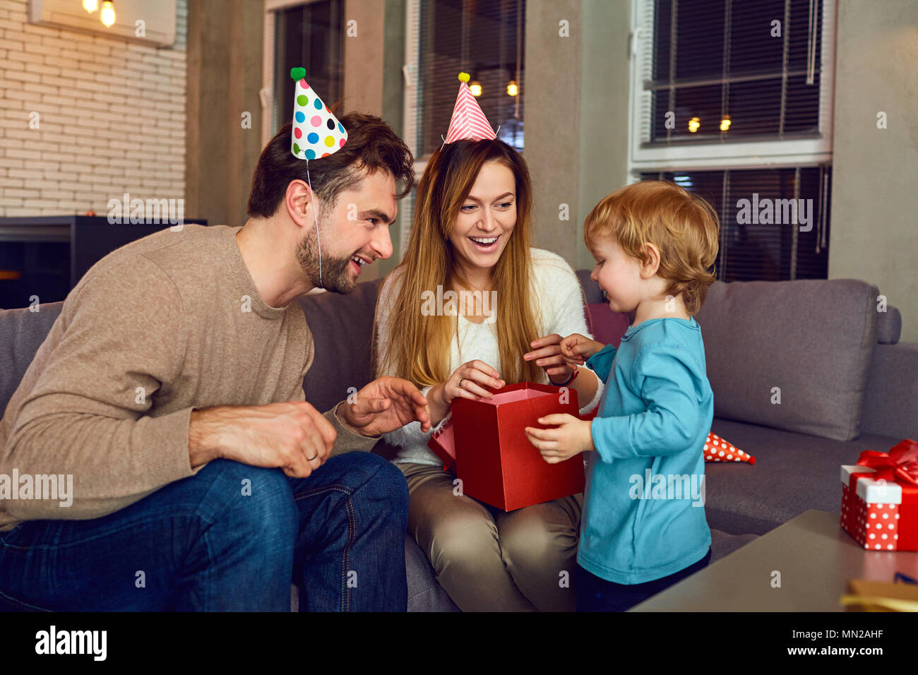 Parents give a gift to their child on the day of birth. - Stock Image