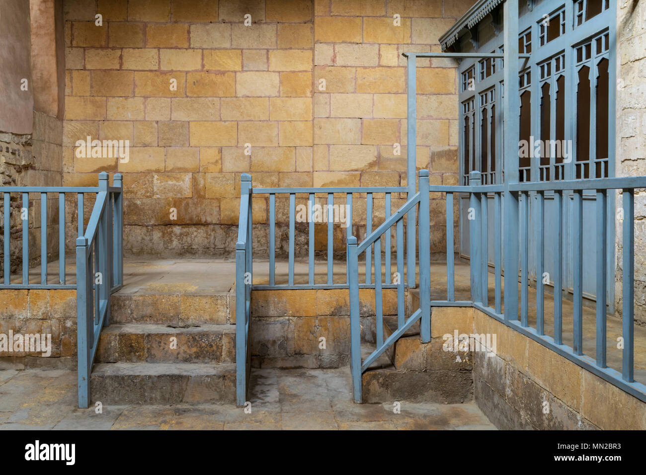 Abandoned historic traditional bathhouse (Hamam Inal) with staircase leading to bricks stone wall, wooden blue balustrade, and doors of changing rooms - Stock Image