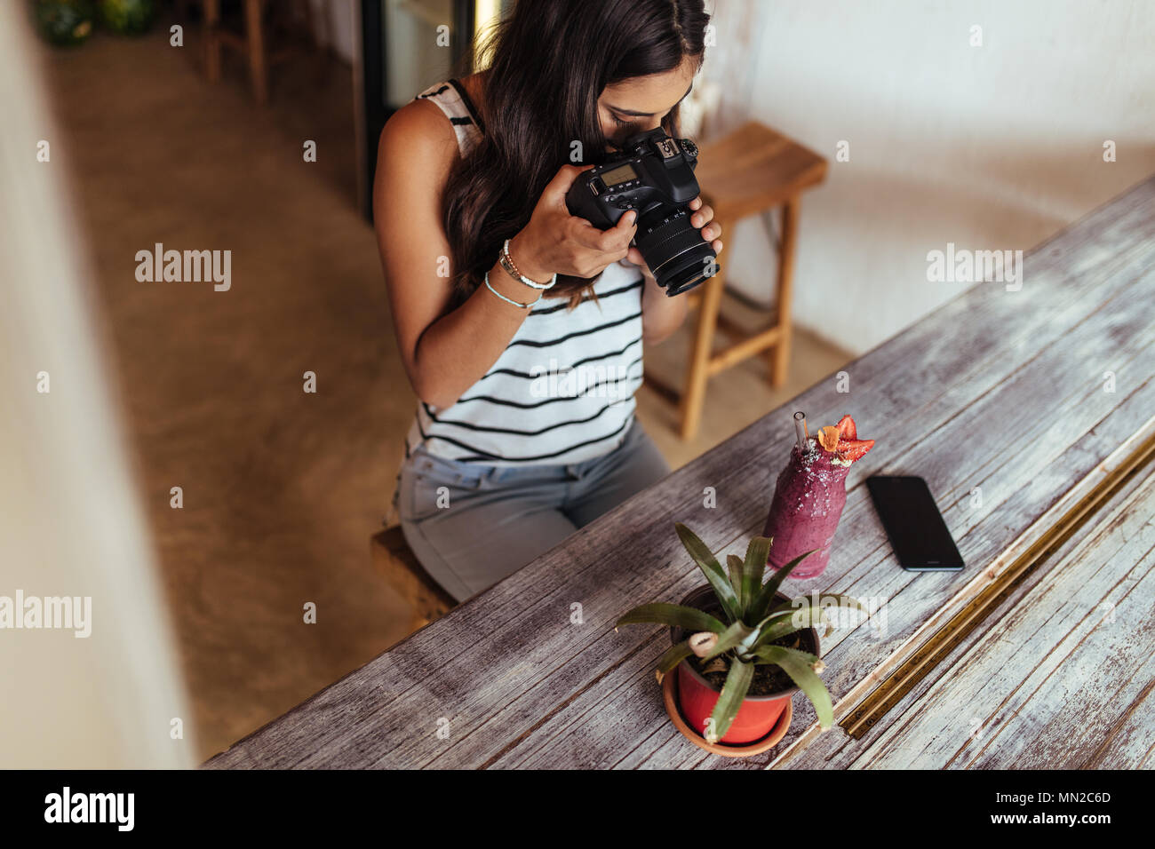 Woman taking photos of a smoothie placed beside a flower pot using a professional camera for her food blog. Food blogger shooting photos for her blog  - Stock Image