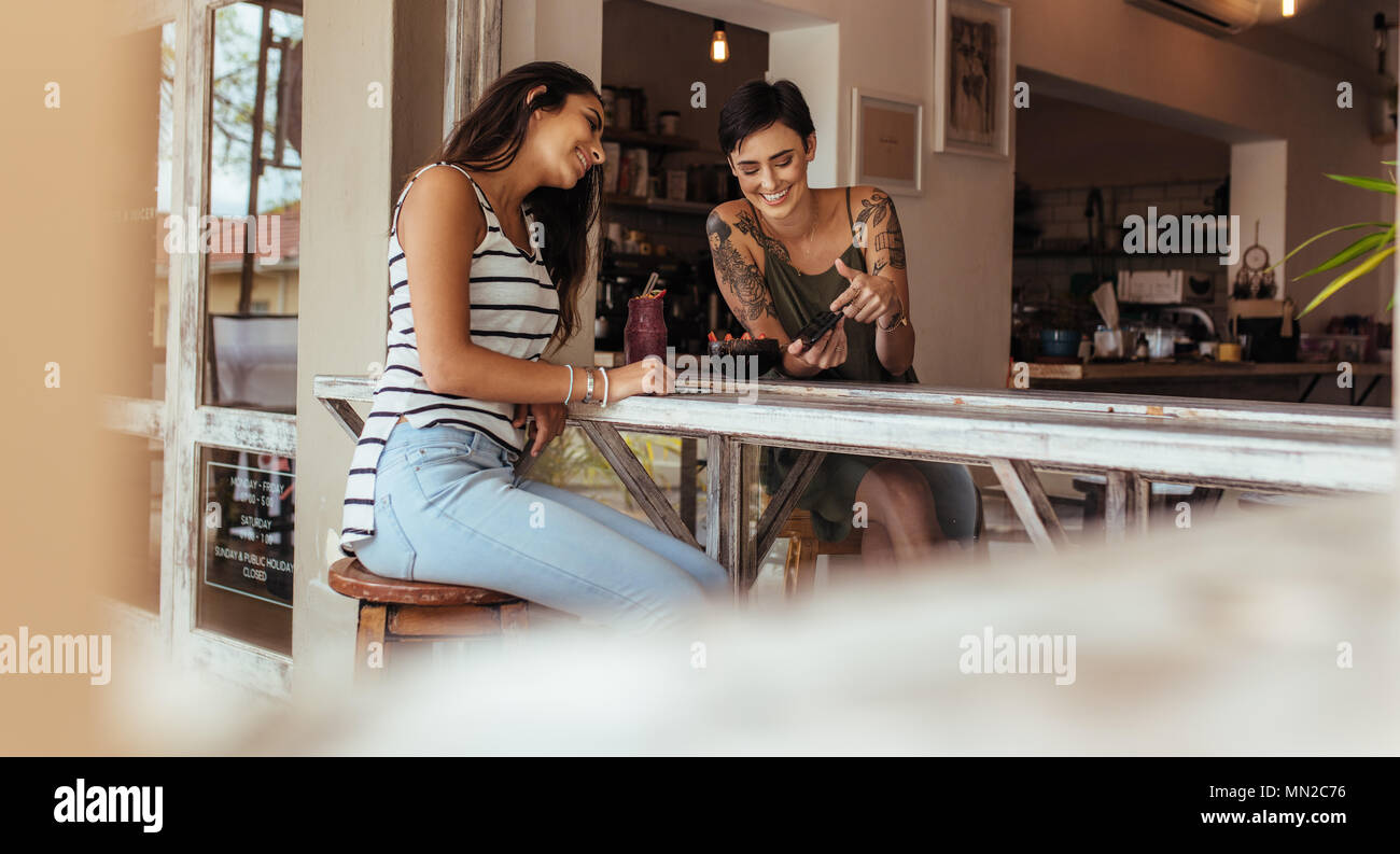 Friends looking at photos in mobile phone while sitting at home with a fruit bowl and smoothie on the table. Two women bloggers sharing ideas on flood - Stock Image