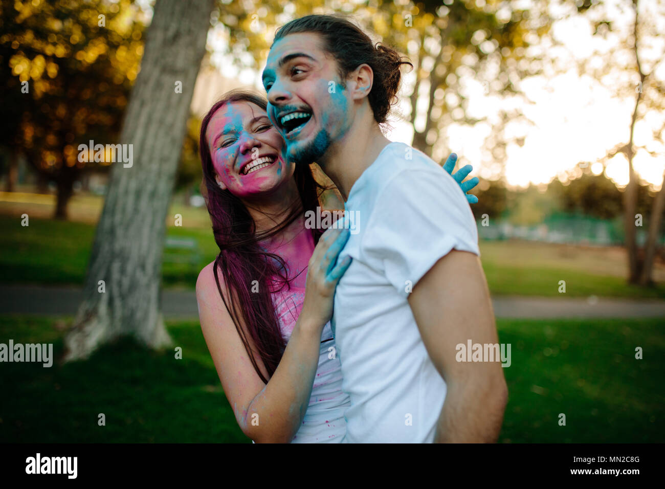 Smiling young couple with colored powder smeared on their faces. Cheerful man and woman enjoying festival of colors outdoors at park. - Stock Image