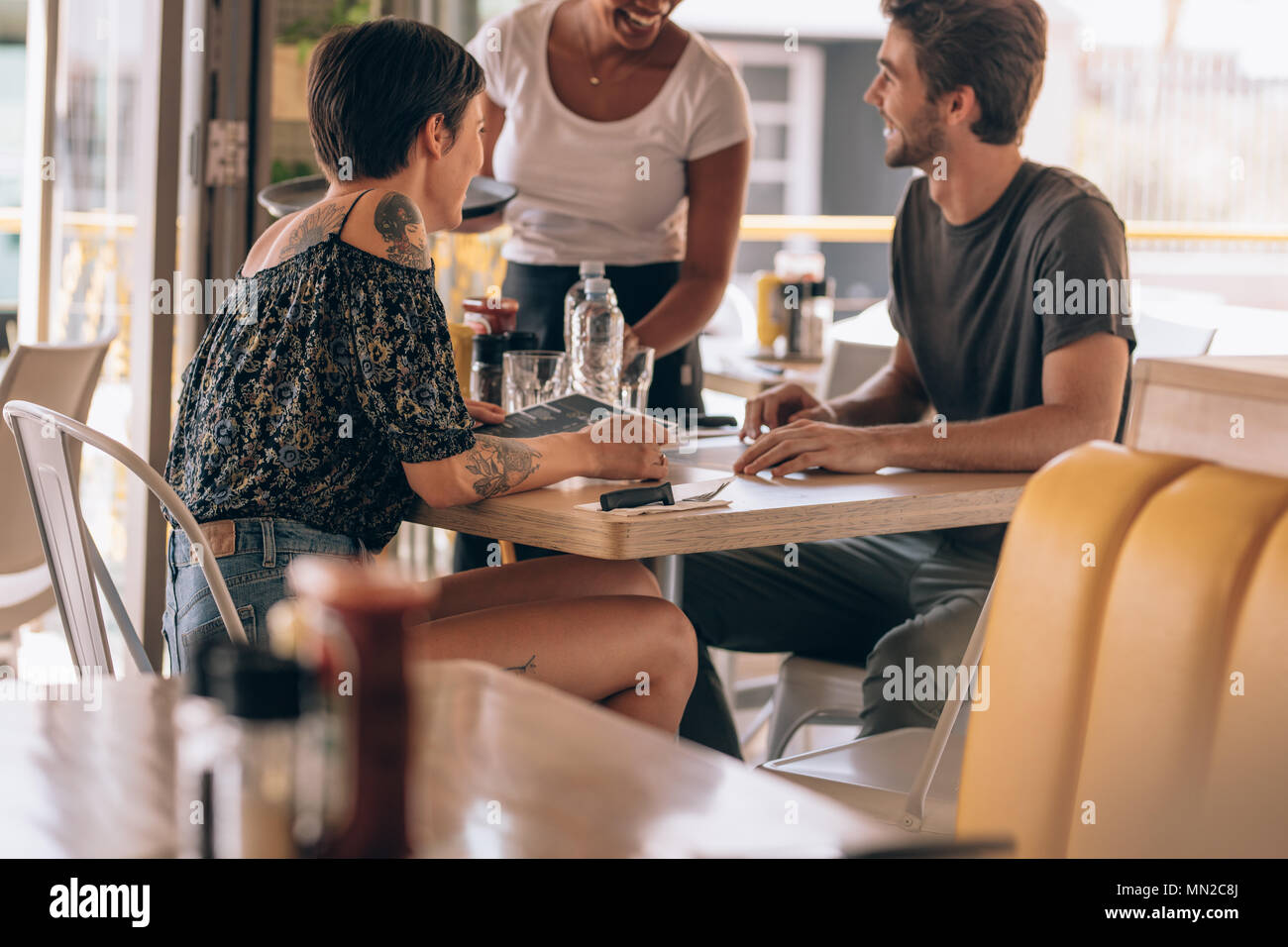 Young couple sitting at cafe giving order to a female waiter. Man placing order to a waitress at restaurant while sitting with his girlfriend. - Stock Image
