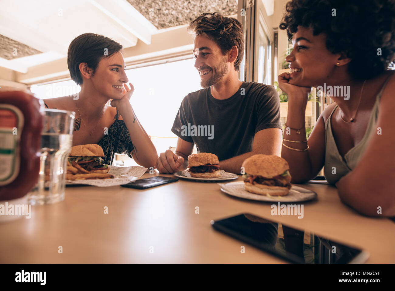 Group of friends sitting at a restaurant with a stacked burgers on the table. Happy young man with his female friends sitting together at cafe and hav Stock Photo