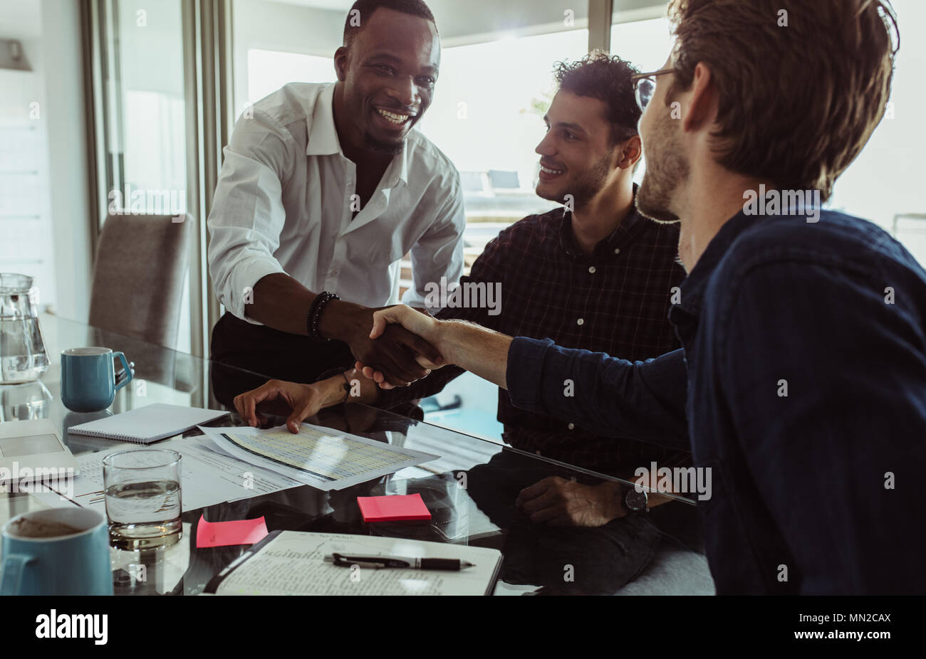Businessmen discussing work sitting at conference table in office. Men shaking hands and smiling during a business meeting. - Stock Image