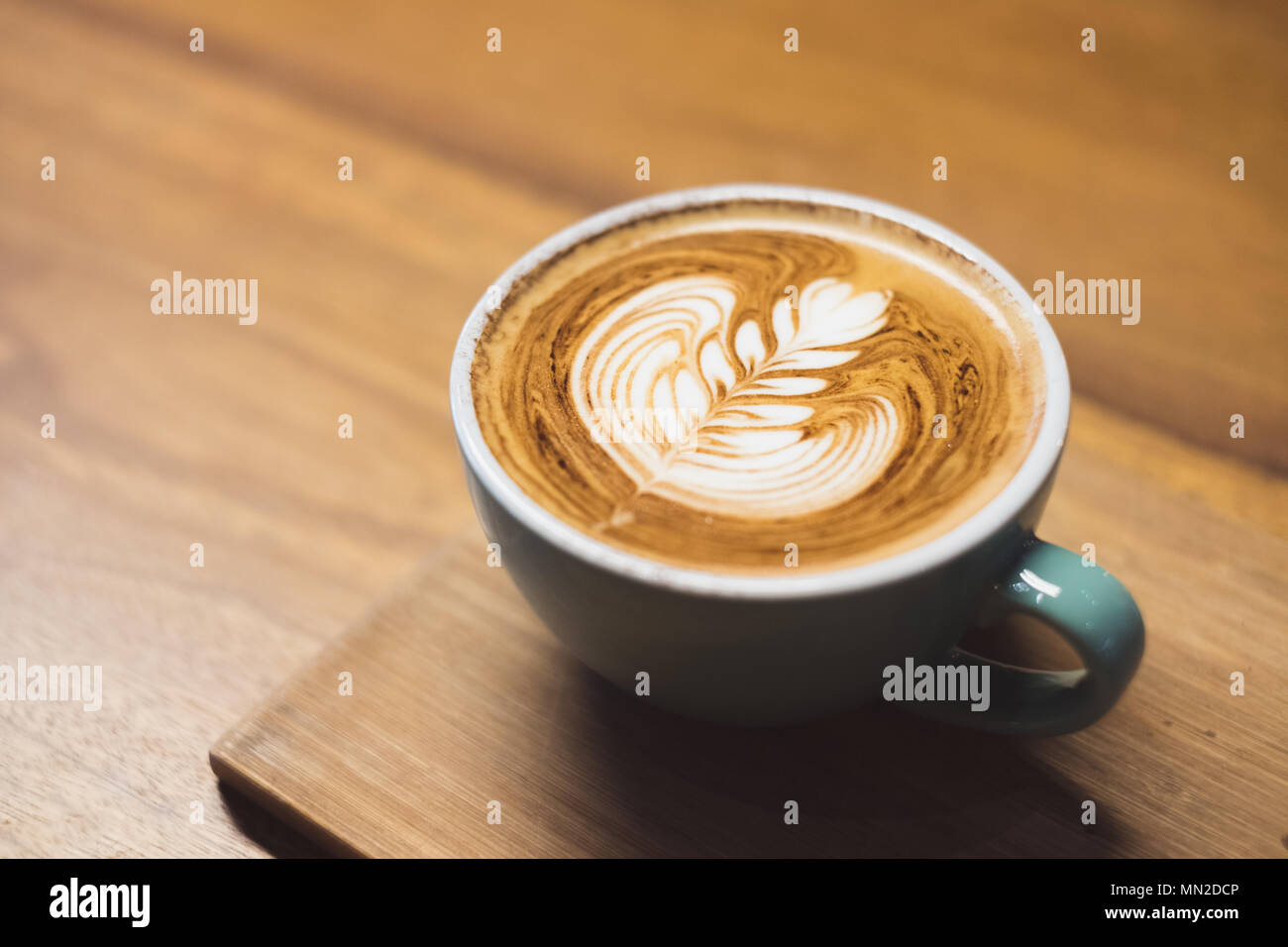 Close up hot cappuccino coffee cup with heart shape latte art on wood table at cafe,Drak tone filter,food and drink - Stock Image