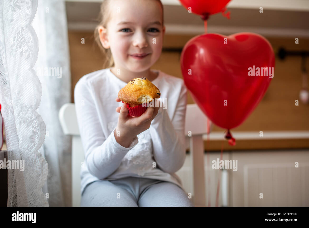 Cute preschooler girl celebrating 6th birthday. Girl eating her birthday cupcake in the kitchen, surrounded by balloons. - Stock Image