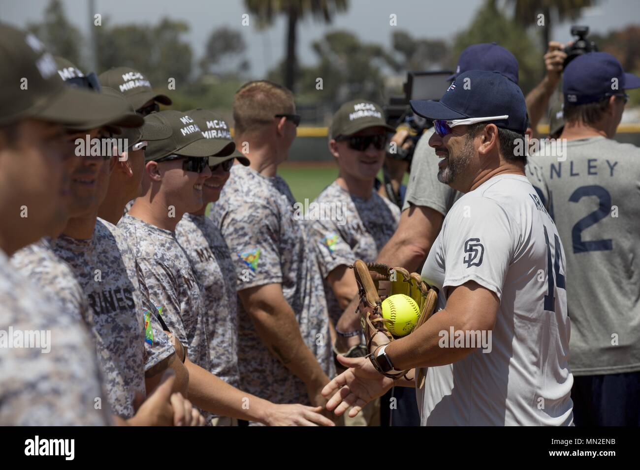 Marines with Marine Corps Air Station Miramar's softball team and San Diego Padres Alumni shake hands prior to playing a softball game on MCAS Miramar, Calif. May 10, May 10, 2018. The Padres Alumni came to demonstrate their support for the military with spirited competition and to thank service members of MCAS Miramar for their service. (U.S. Marine Corps photo by Cpl. Daniel Auvert/Released). () - Stock Image