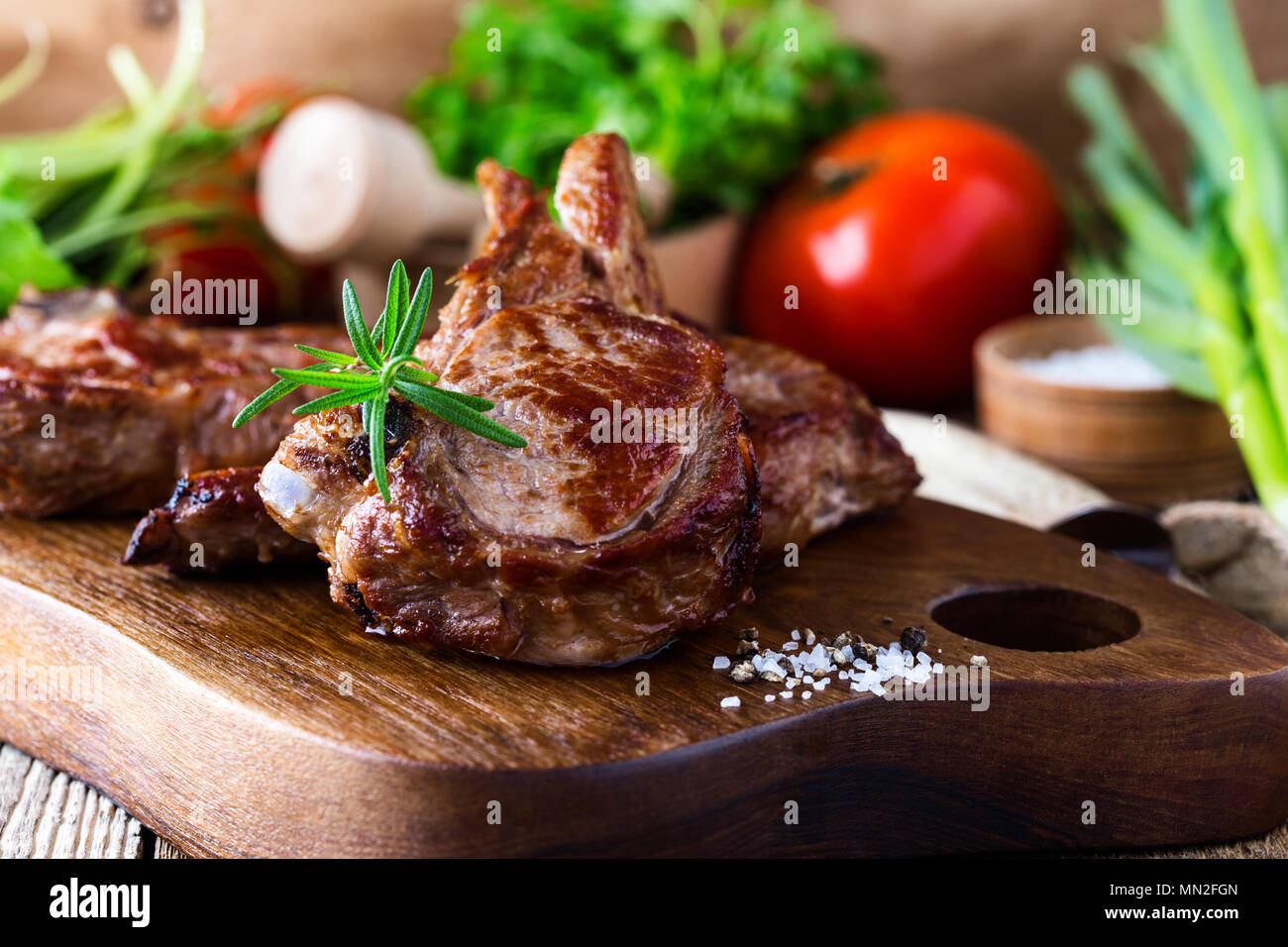 Roasted veal chops with fresh herbs and vegetables on rustic wooden cutting board, pan seared steak dinner - Stock Image