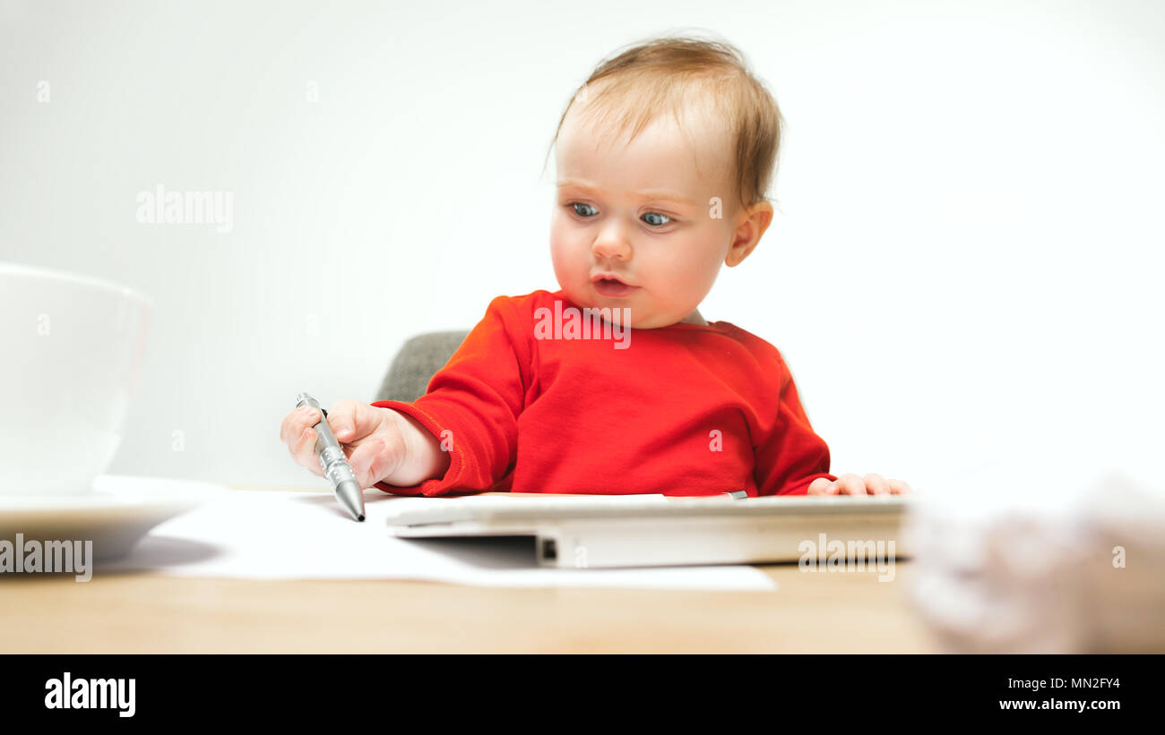 Happy child baby girl sitting with pen and keyboard of modern computer or laptop isolated on