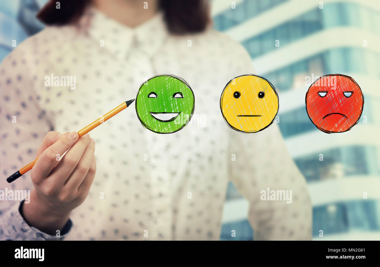 Young woman close up holding a pencil in hand choosing smiling emoticon rating. Excellent customer service concept. - Stock Image