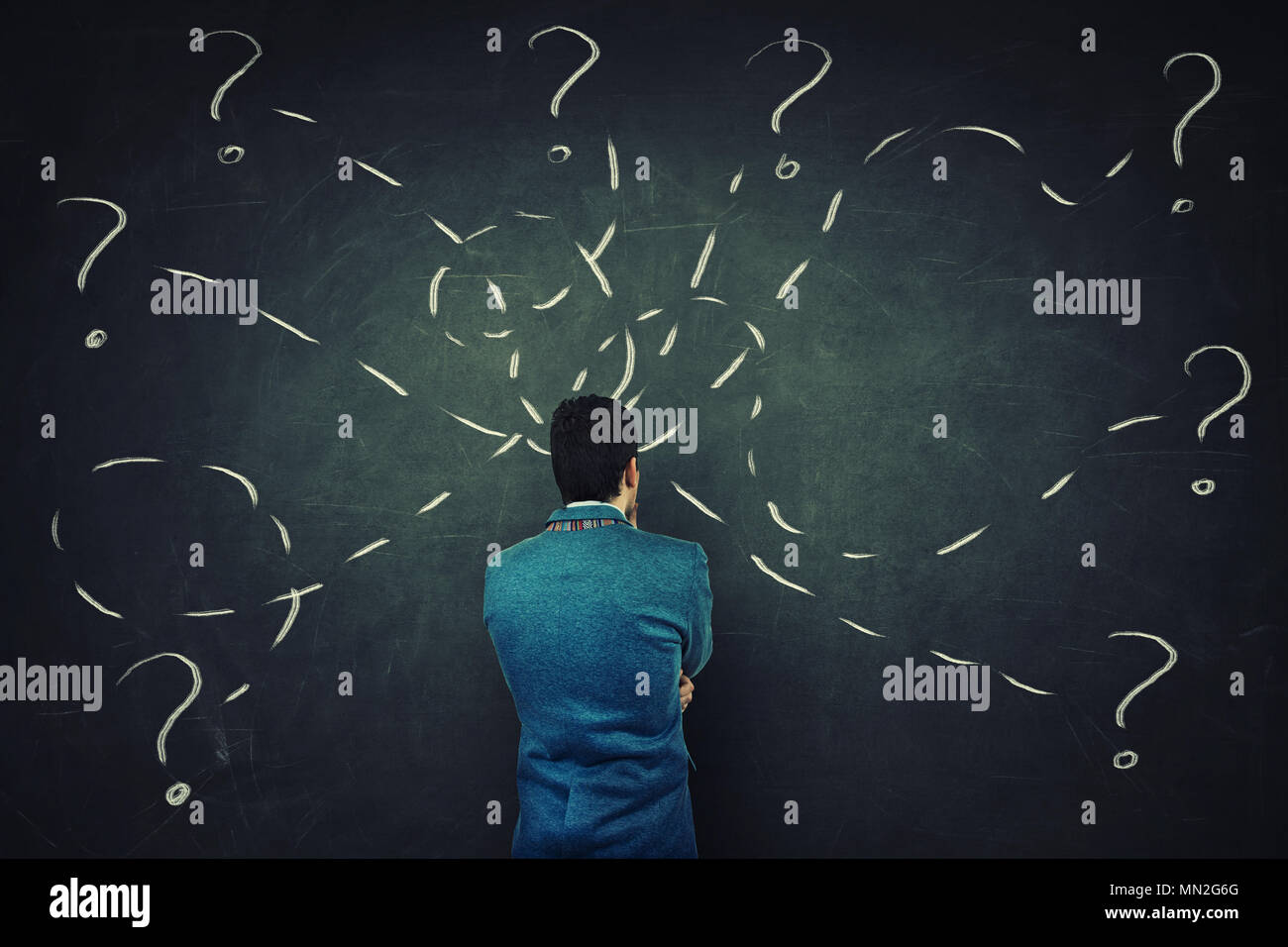 Rear view of a puzzled businessman in front of a blackboard try to solve different tasks, having questions. - Stock Image