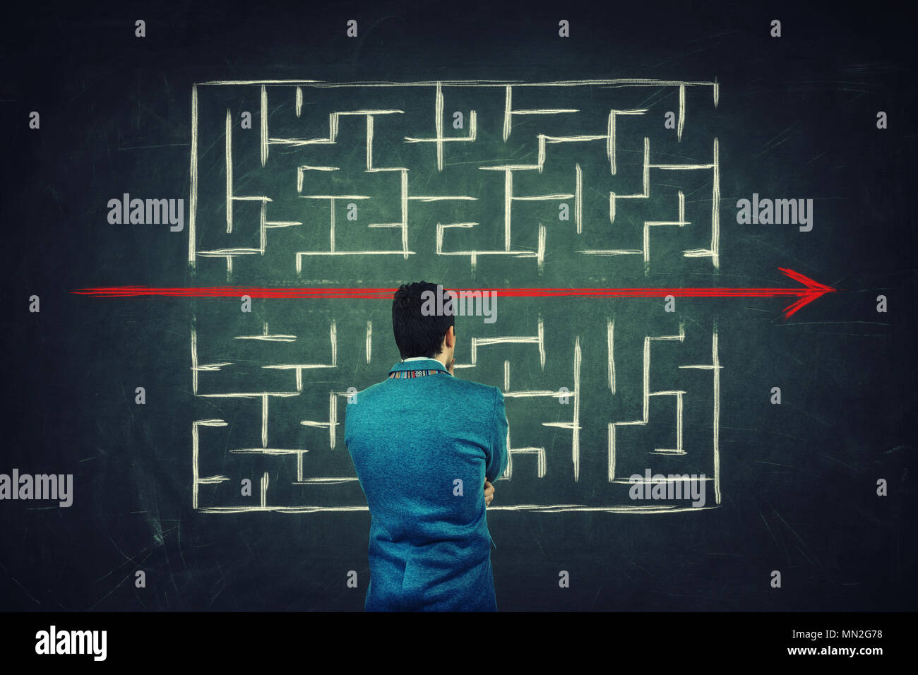 Rear view of a puzzled businessman in front of a blackboard finding a solution to escape from labyrinth. Breaking the rules, as a red line pierce the  - Stock Image
