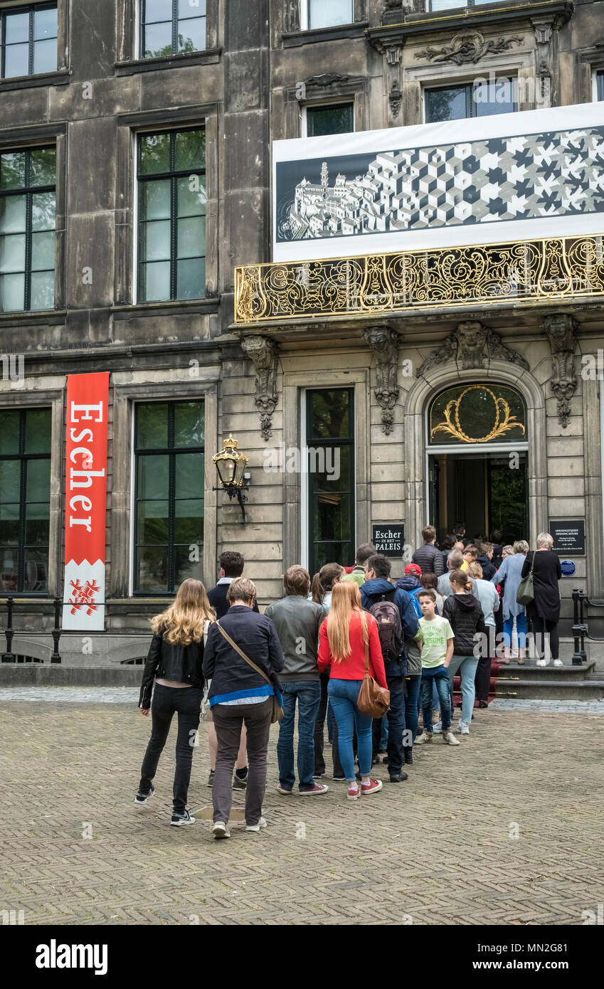 People queue outside the entrance to Escher in Het Paleis, to see works by Dutch artist M.C. Escher, Lange Voorhout Palace, The Hague, Netherlands. Stock Photo