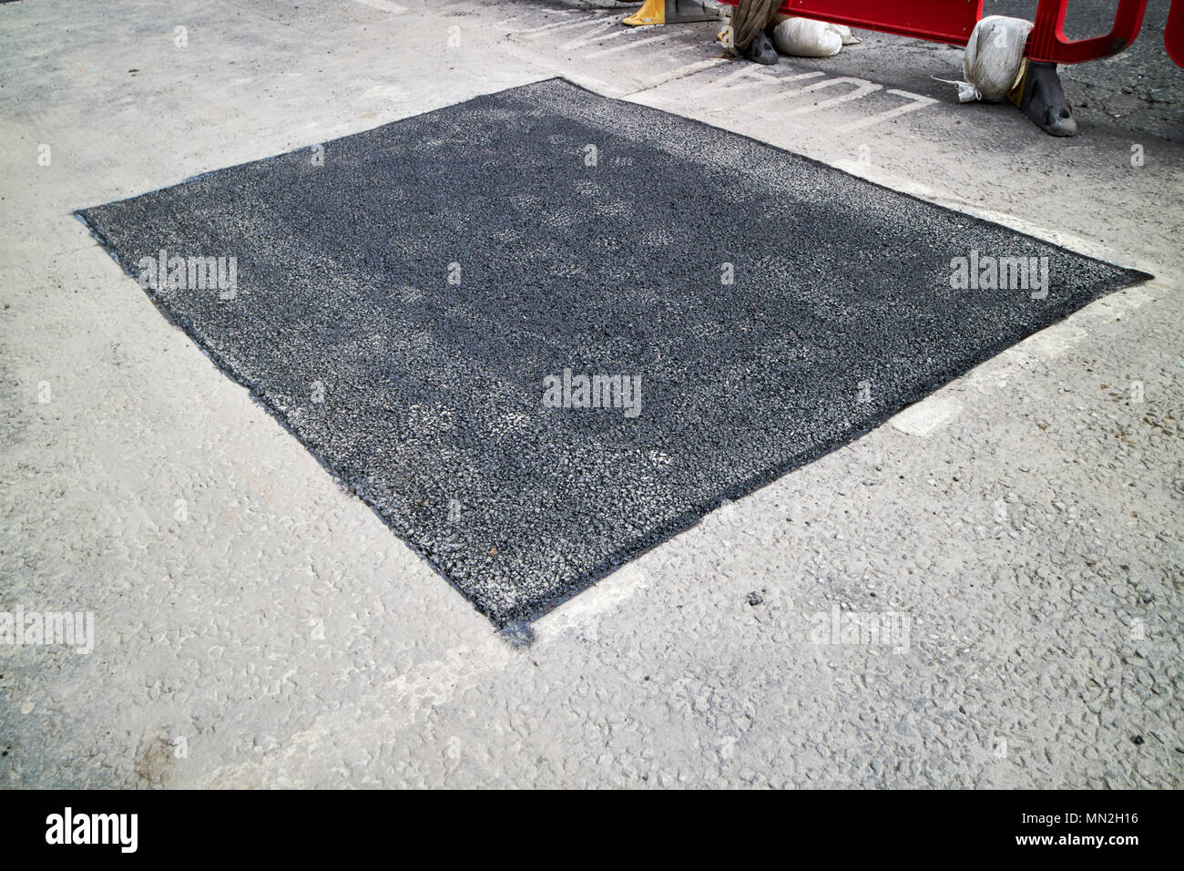 freshly laid section of tarmac to repair series of potholes in the road England UK - Stock Image