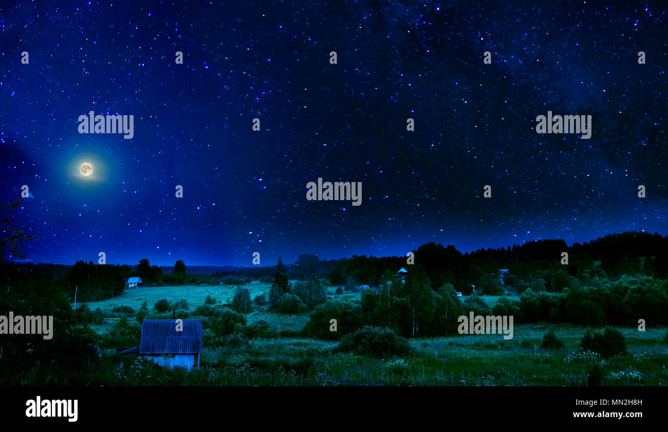 Summer rural night landscape with a bright flickering starry sky and the full moon over the sleeping blossoming valley and village - Stock Image