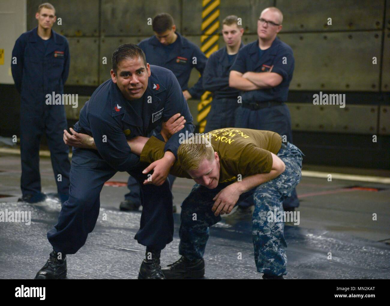 170816-N-NB142-0985   PACIFIC OCEAN (Aug. 16, 2017) Master-at-Arms 1st Class Gabriel Suarez and Legalman 1st Class John Detty demonstrate a mechanical advantage control hold (MACH) takedown during a Security Reaction Force Basic course in the well deck of the Wasp-class amphibious assault ship USS Essex (LHD 2). Essex is underway conducting sea trials and flight deck certifications off the coast of Southern California. (U.S. Navy photo by Mass Communication Specialist 3rd Class Chandler Harrell/Released) - Stock Image