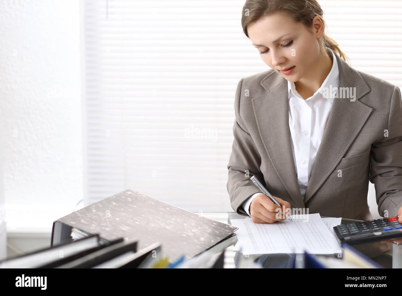 Portrait of female bookkeeper or financial inspector  making report, calculating or checking balance. Copy space area  - Stock Image