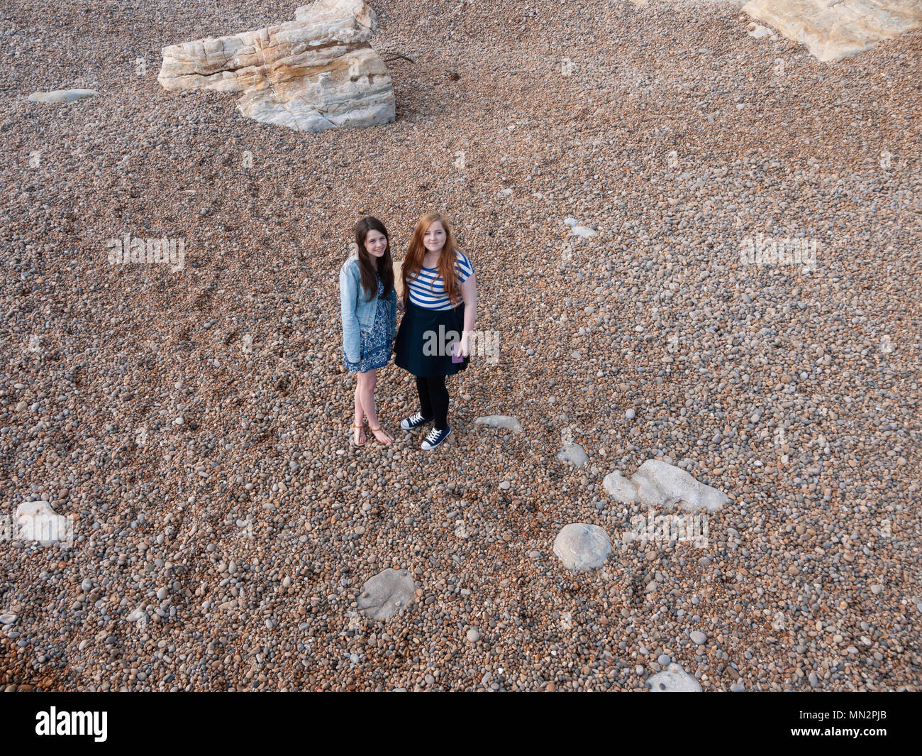 Two young ladies on a pebble beach - Stock Image