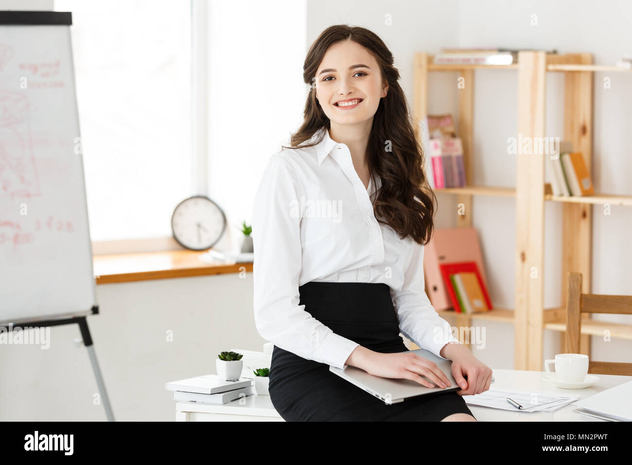 Young pretty business woman with notebook and document in the bright modern office indoors Stock Photo