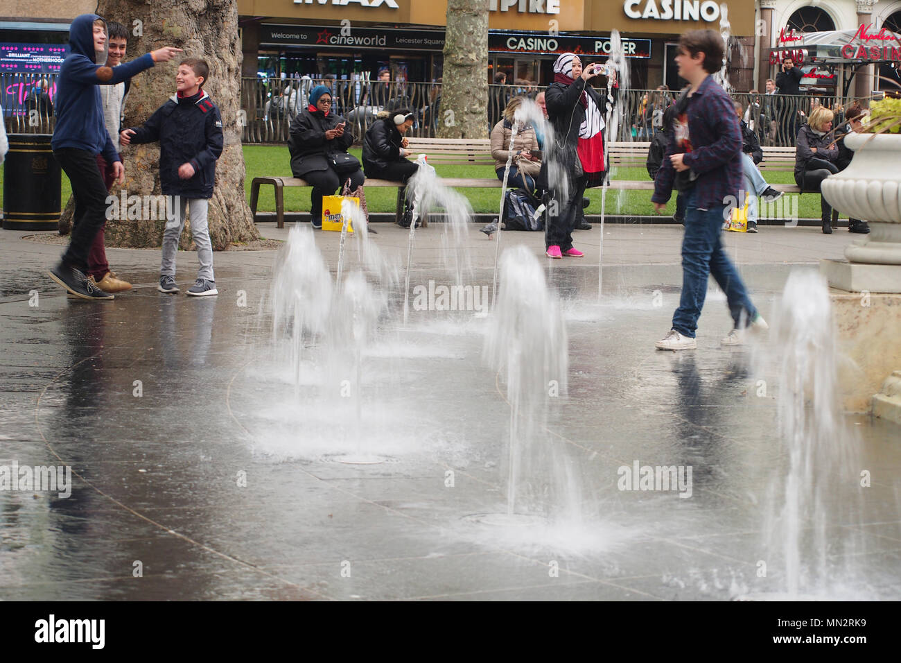 Male teenagers playing in the water feature fountains in Leicester Square, London - Stock Image