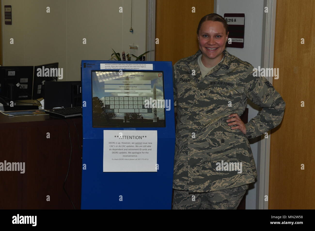 Staff Sgt. Megan Storms, 90th Force Support Squadron, reenlistments, extensions, enlisted promotions and retraining NCO in charge, poses near the new customer kiosk machine located at the Military Personnel Flight office at F.E. Warren Air Force Base, Wyo., August 9, 2017. The new system was installed to alleviate long wait times. (U.S. Air Force photo by Terry Higgins) - Stock Image