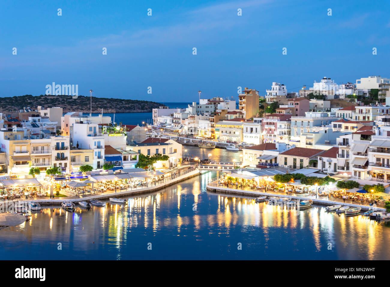 View of town and harbour at dusk, Agios Nikolaos, Lasithi Region, Crete (Kriti), Greece - Stock Image