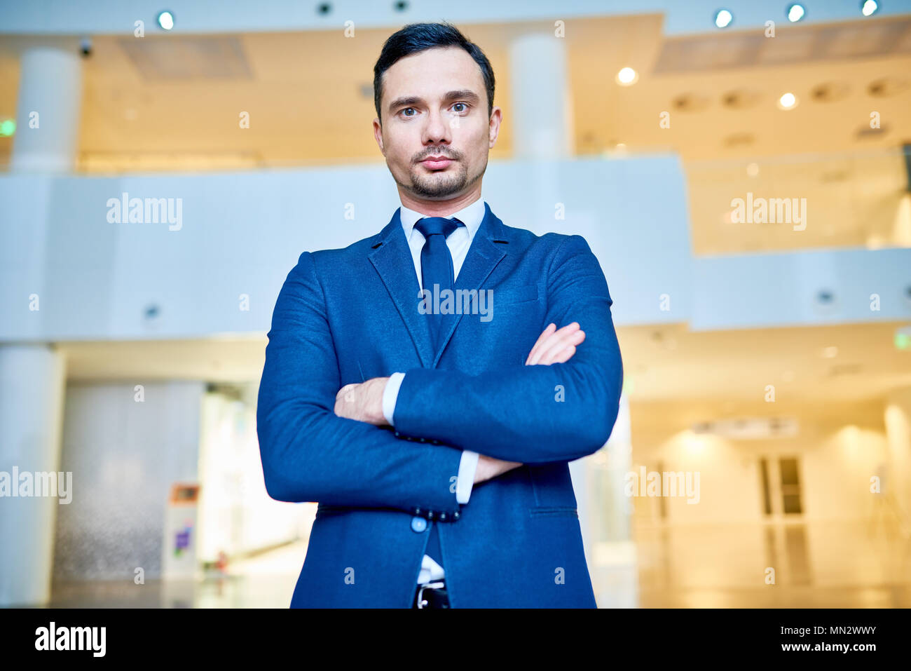 Waist up portrait of successful young businessman wearing blue suit posing confidently and looking at camera while standing with arms crossed in moder Stock Photo