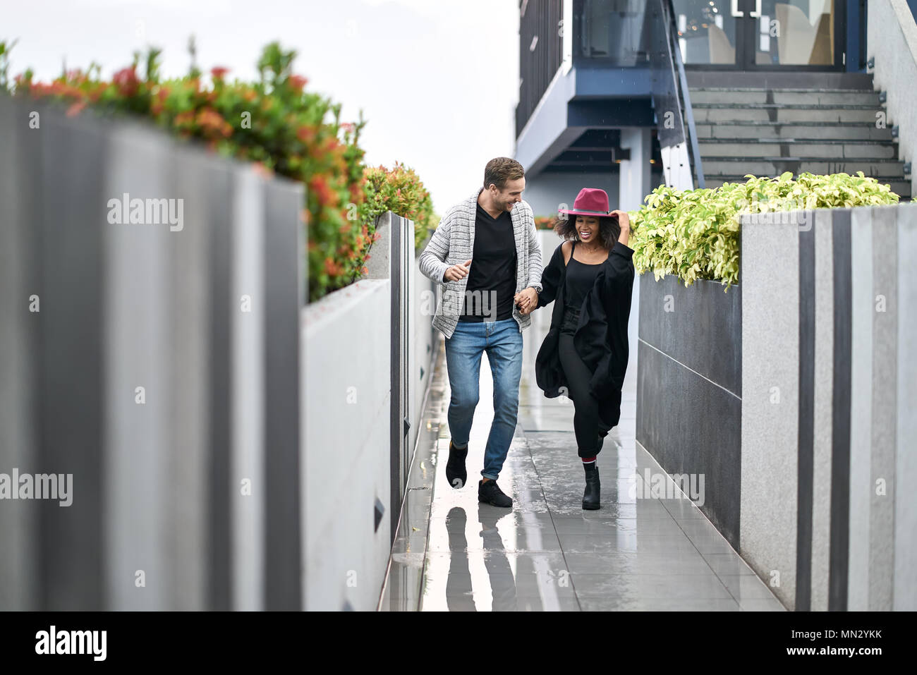 Laughing interracial couple is running from the rain on the open terrace in the building. Black girl wears dark clothes with a crimson hat, white guy  - Stock Image
