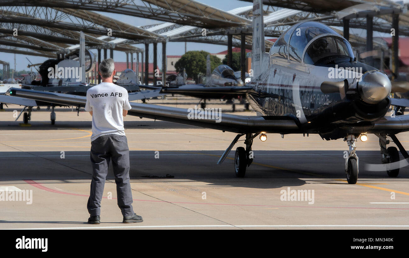 An L3 Communications crew chief communicates with a T-6 Texan II team at Vance Air Force Base, Oklahoma, Aug. 28. Since 1960, Vance Airmen have teamed up with contract partner civilians like those from L3 to support the training of tomorrow's fliers. (U.S. Air Force photo by David Poe) - Stock Image