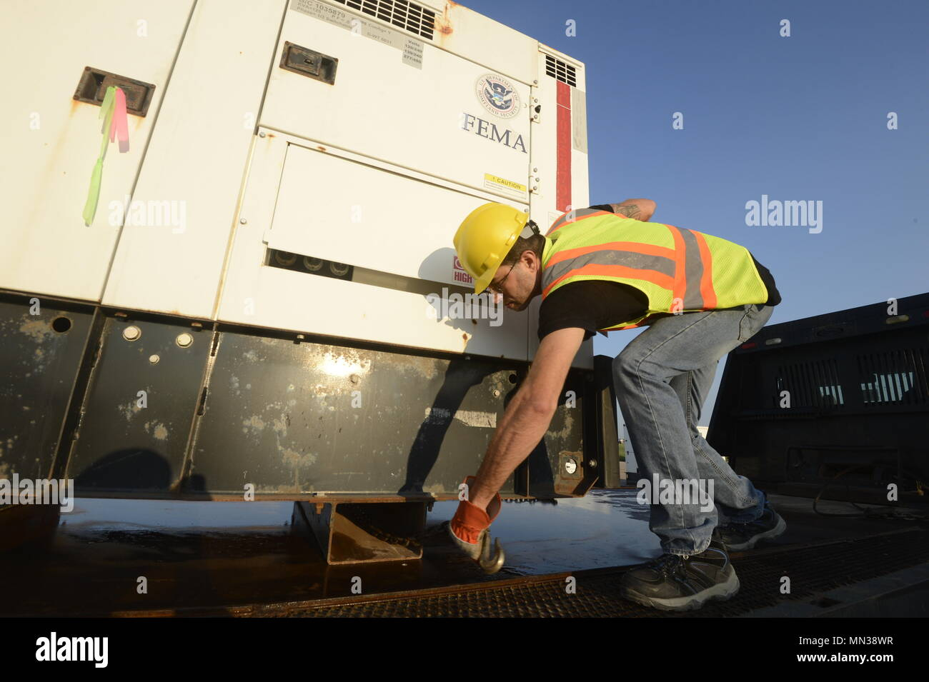 Jerry Wales, contractor, attaches support chains to a Federal Emergency Management Agency diesel generator to be used in support Hurricane Harvey relief efforts, at JBSA Randolph auxiliary airfield, Seguin, Texas, August 31, 2017. The category-4 hurricane, with wind speeds of 130 mph, made landfall August 25, 2017.  Days after the hurricane reached Texas, more than 50 inches of rain flooded the coastal region. (U.S. Air Force Photo by Tech. Sgt. Chad Chisholm/Released) Stock Photo