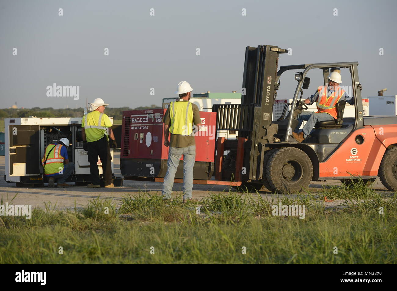 ACI contractors move a Federal Emergency Management Agency generator in support of Hurricane Harvey relief efforts, at JBSA Randolph auxiliary airfield, Seguin, Texas, August 31, 2017. The category-4 hurricane, with wind speeds of 130 mph, made landfall August 25, 2017.  Days after the hurricane reached Texas, more than 50 inches of rain flooded the coastal region. (U.S. Air Force Photo by Tech. Sgt. Chad Chisholm/Released) Stock Photo