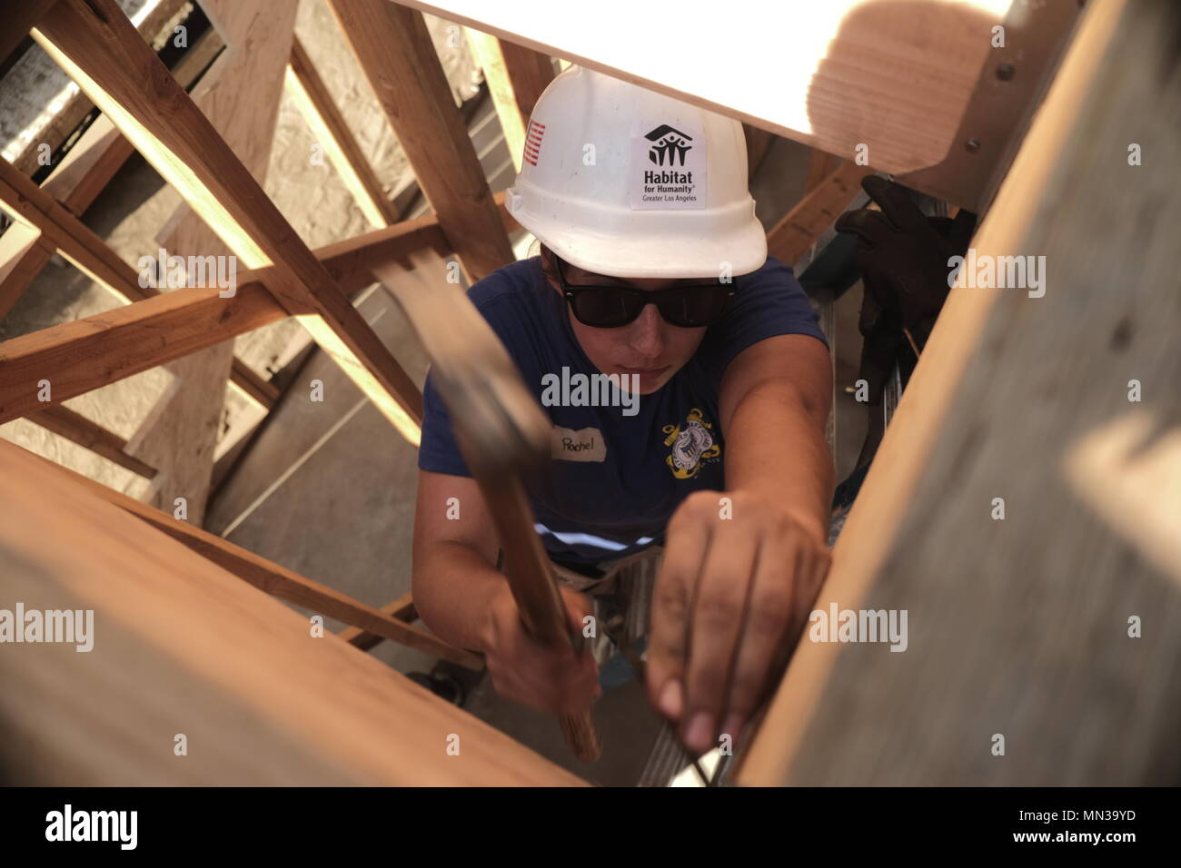 A Coast Guard servicewoman hammers nails into a building frame during the contruction of a townhouse hosted by Habitats for Humanity in Long Beach, Calif., as part of LA Fleet Week 2017, Aug. 31. LA Fleet Week is an opportunity for the American public to meet their Navy, Marine Corps and Coast Guard team and experience America's sea services. During fleet week, service members will participate in various community service events, showcase capabilities and equipment to the community, and enjoy the hospitality of Los Angeles and surrounding areas have to offer. (U.S. Marine Corps photo by Cpl. D - Stock Image