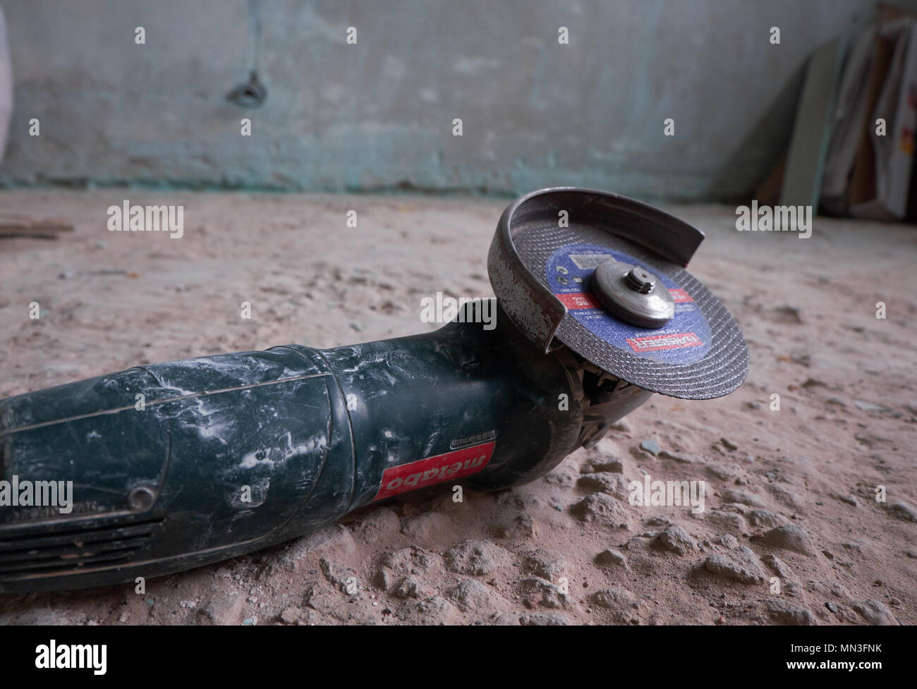 Side grinder on a floor in front of a dirty wall. Overhaul concept - Stock Image