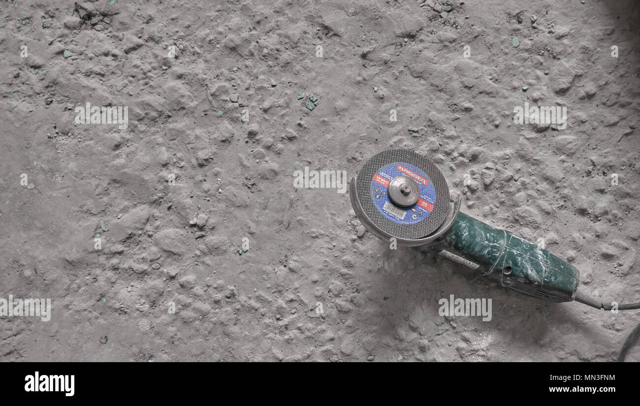 Angle grinder on a old dirty concrete floor. Overhaul concept - Stock Image