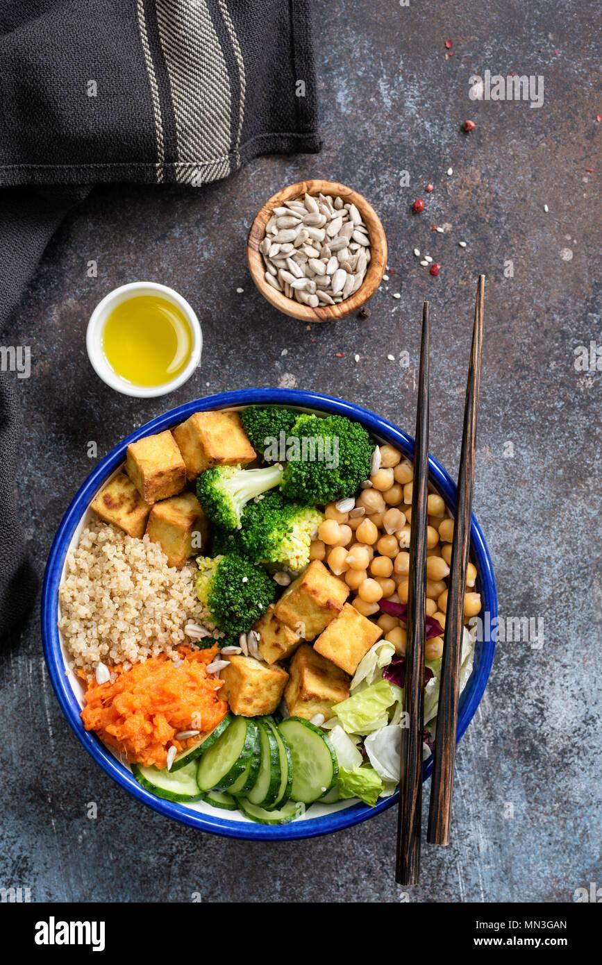Buddha Bowl with quinoa, tofu, broccoli, sweet potato and cucumber. Nourishing buddha bowl. Healthy vegan or vegetarian salad bowl, table top view - Stock Image