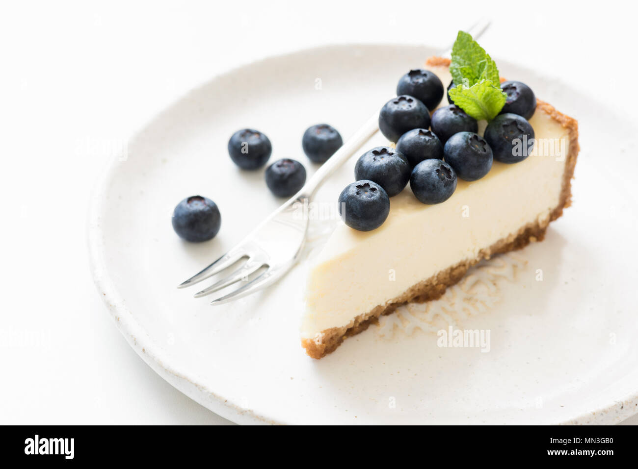 Slice of cheesecake with blueberries and mint leaf on white. Closeup view, selective focus. New York cheesecake - Stock Image