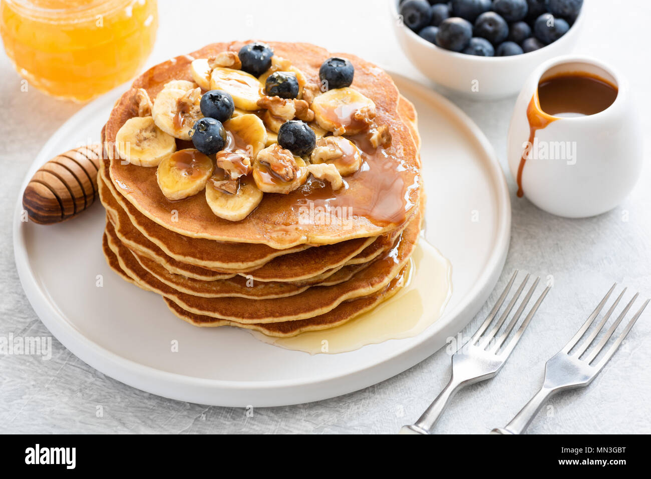 Stack of pancakes with banana, blueberries, walnuts, honey and caramel sauce on white plate. Closeup view. Breakfast pancakes with maple syrup - Stock Image