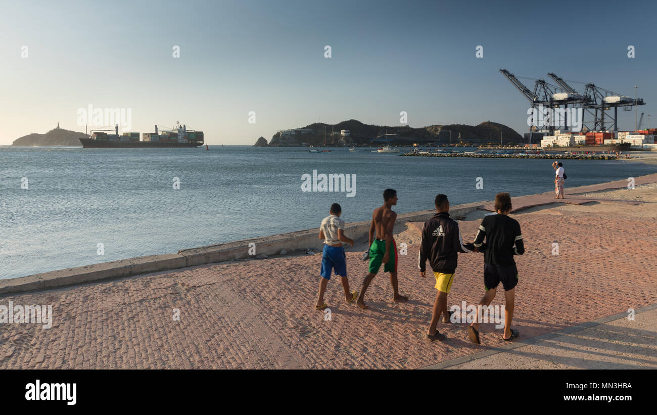 The Malecon (waterfront) and port with an inbound container ship, Santa Marta, Magdalena, Colombia - Stock Image