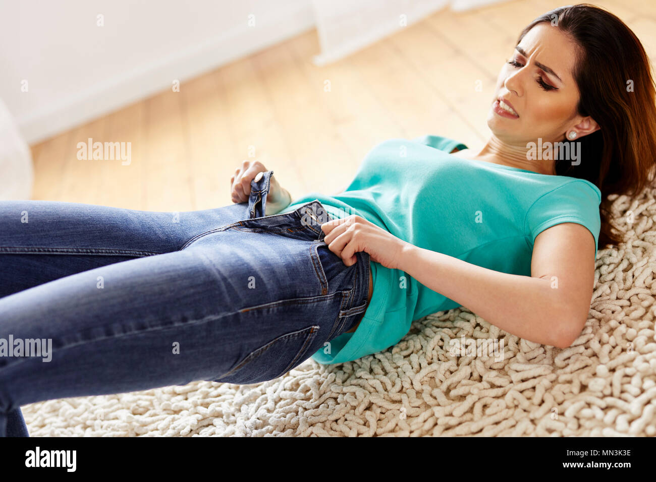 Girl pulling up tight fitted jeans - Stock Image